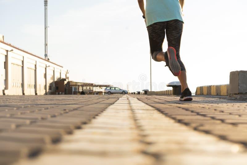 разминка женщины здоровья восхода солнца идущего ботинка бегунка дороги jog пригодности ног принципиальной схемы крупного плана К стоковое фото rf