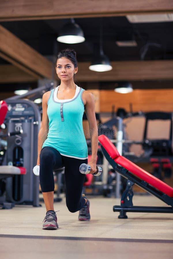 Разминка женщины с гантелями в спортзале фитнеса стоковые изображения