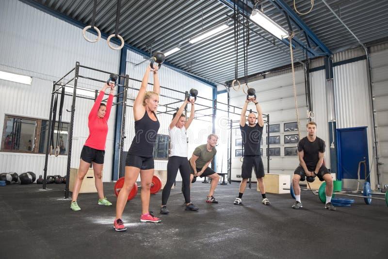Разминка команды с kettlebells на спортзале фитнеса стоковое изображение rf