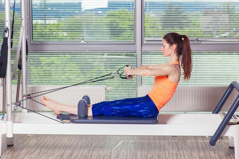 Разминка реформатора Pilates работает женщину на спортзале крытом стоковое изображение rf