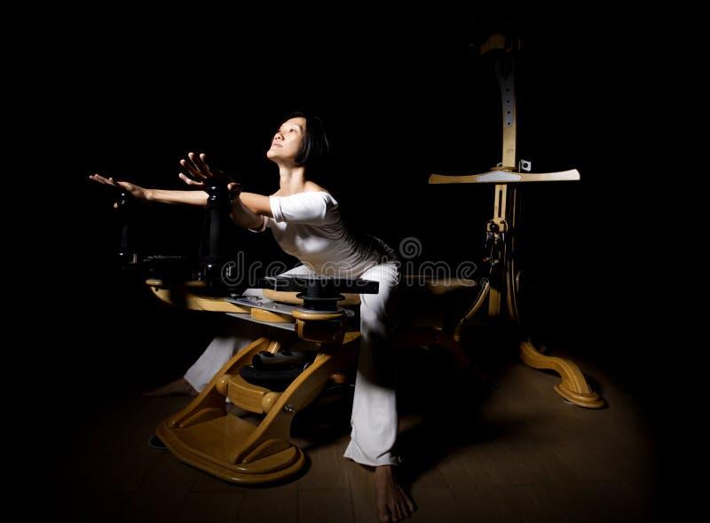 Разминка реформатора Pilates работает женщину стоковое фото