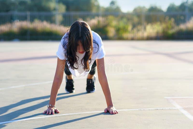 Разминка тела ядра - женщина фитнеса делая планку Девушка пригонки делая тренировку планки на открытом воздухе в стадионе на солн стоковое фото rf