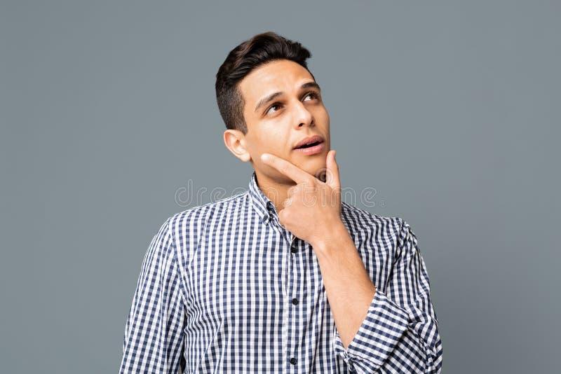 Размышлянный и задумчивый человек в Checkered рубашке касаясь его Chin стоковые изображения
