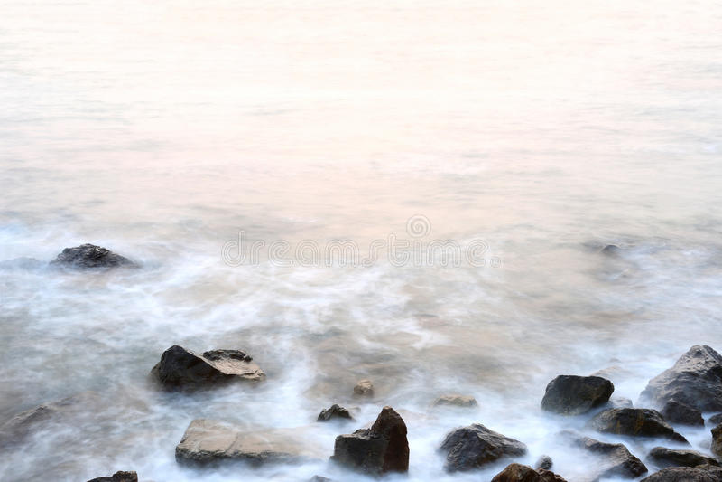 Размягченность тумана моря приливов и захода солнца на вечере с утесами стоковое изображение
