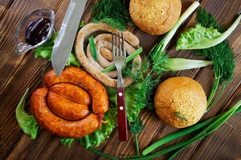 Разнообразие зажаренная плюшка сосисок, соуса, вилки, ножа и мозоли на деревянной поверхности с зелеными цветами: салат, укроп и  стоковая фотография rf