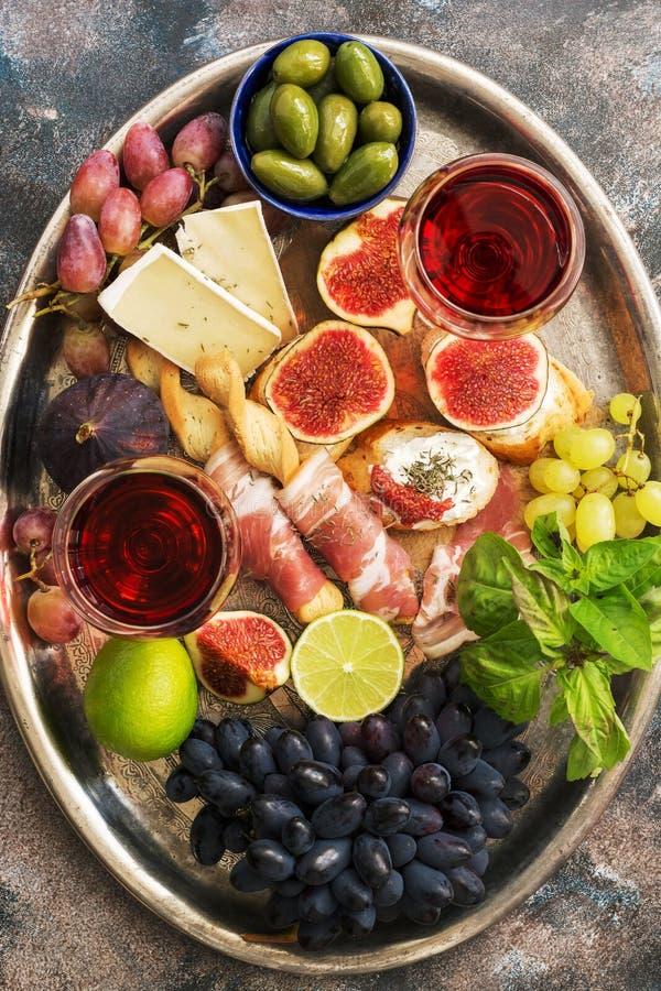 Разнообразие закуска, ветчина, виноградины, вино, сыр с прессформой, смоквами, оливками на подносе металла Среднеземноморская зак стоковые изображения rf