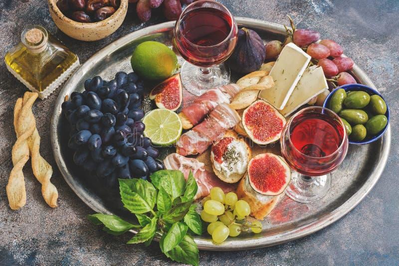 Разнообразие закуска, ветчина, виноградины, вино, сыр с прессформой, смоквами, оливками на подносе металла Среднеземноморская зак стоковая фотография rf