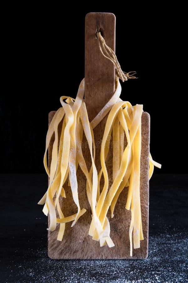 Разнообразие итальянские домодельные сырцовые сырые макаронные изделия tagliatelle на разделочной доске с красивый освещать контр стоковое изображение