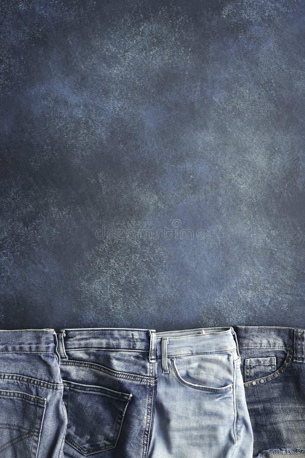 Разнообразие людей и джинсов woomen на предпосылке grunge Взгляд сверху с космосом для текста стоковая фотография
