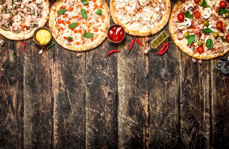 разнообразие пицц На деревянной предпосылке стоковая фотография rf