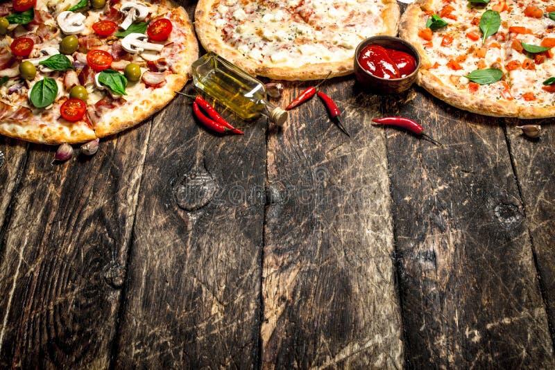 разнообразие пицц На деревянной предпосылке стоковое изображение