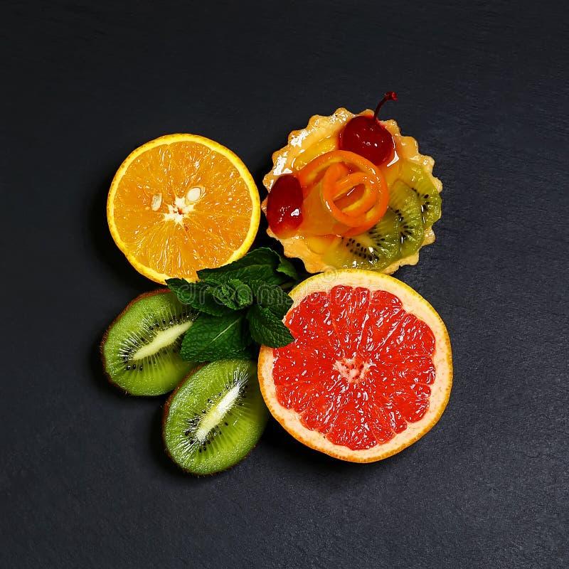 Разнообразие плодоовощей грейпфрута, апельсинов, кивиа, лимона, мяты, торта, сладостного десерта плодоовощ образованного совместн стоковое фото rf
