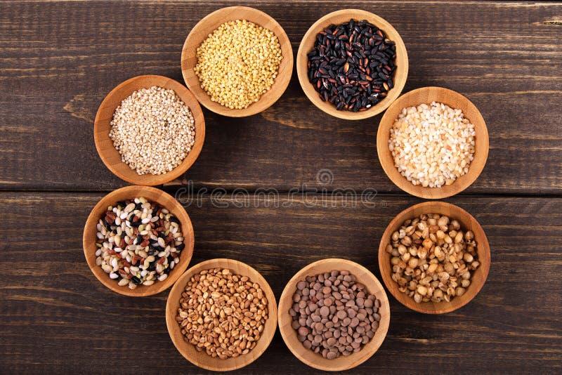 Разнообразие риса и зерен на деревянном столе стоковая фотография rf