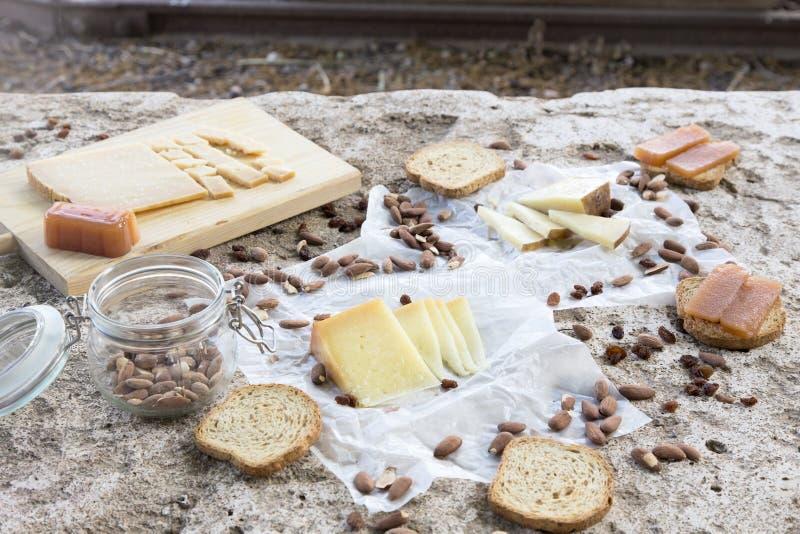Разнообразие сыров, зажаренных в духовке миндалин, здравиц и айвы на камне стоковое фото rf