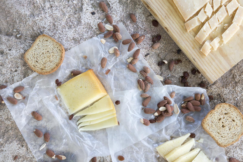 Разнообразие сыров, зажаренных в духовке миндалин, здравиц на каменной таблице стоковое фото rf