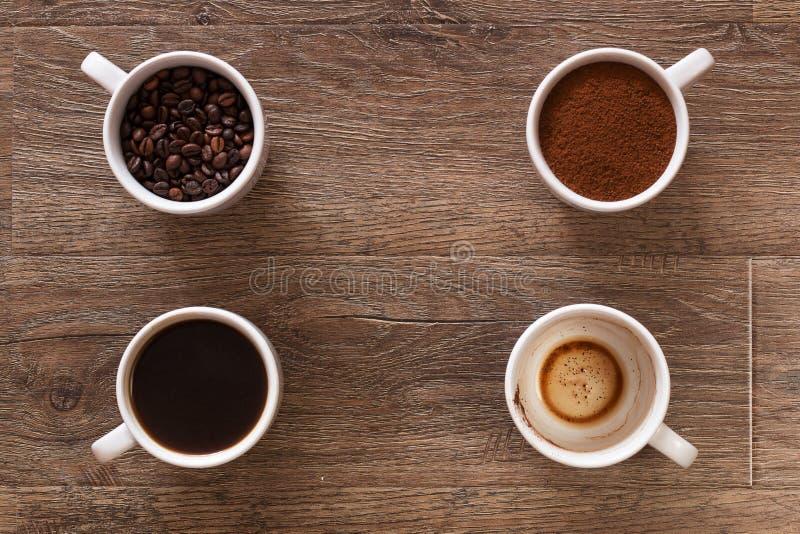 Разнообразие чашек кофе и кофейных зерен на старом деревянном столе 4 чашки кофе, участки питья - фасоли, земли и стоковые фотографии rf