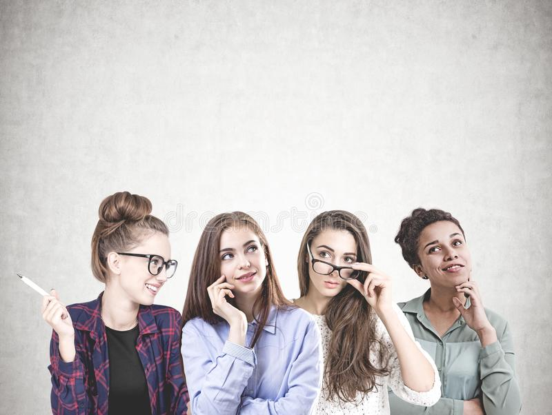 Разнообразная команда молодых женщин, глумится вверх по бетонной стене стоковые изображения