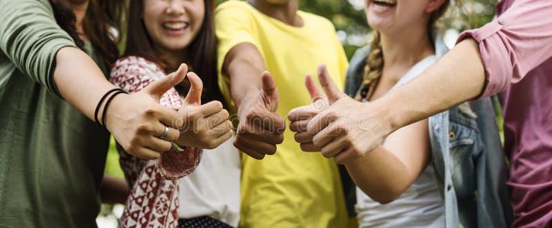 Разнообразное молодые люди большого пальца руки группы вверх по концепции стоковое фото