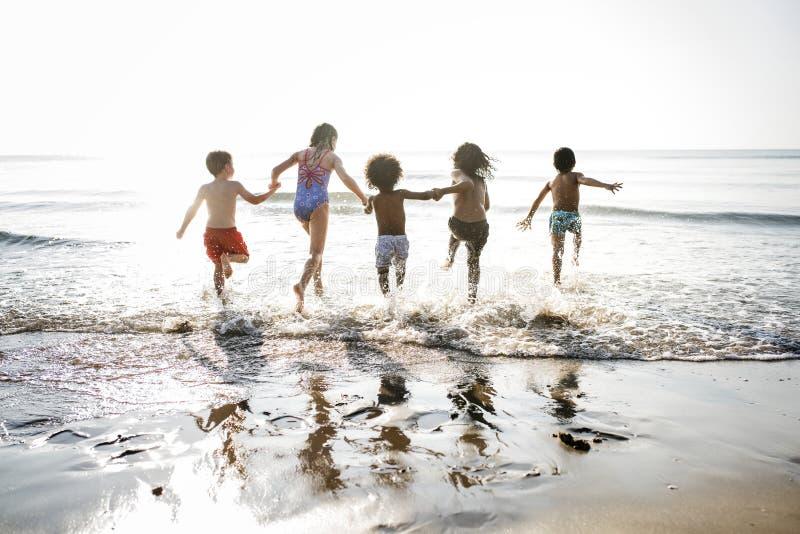 Разнообразные дети бежать на пляже стоковые фотографии rf