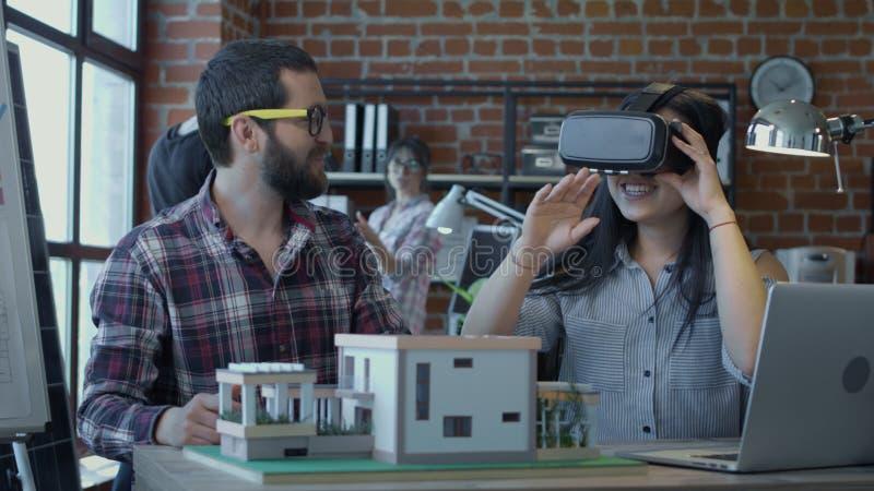 Разнообразные коллеги используя VR пока строящ дом стоковая фотография rf