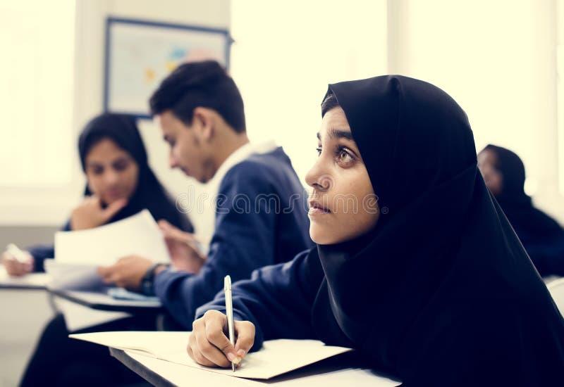 Разнообразные мусульманские дети изучая в классе стоковое фото