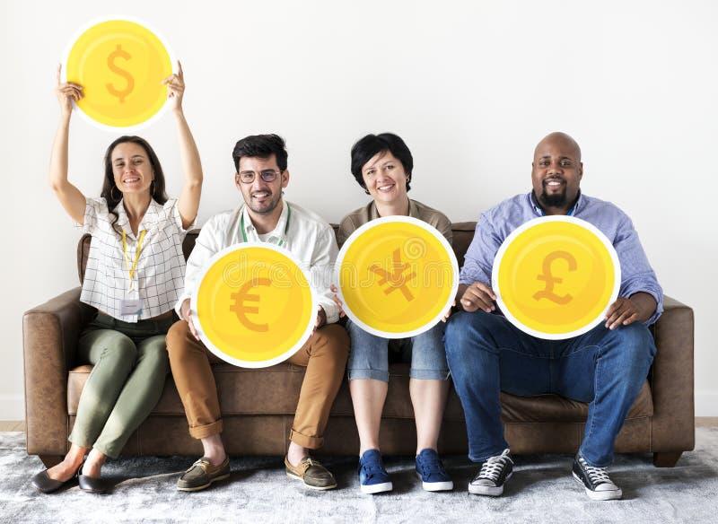 Разнообразные работники сидя и держа значки валюты стоковые фото