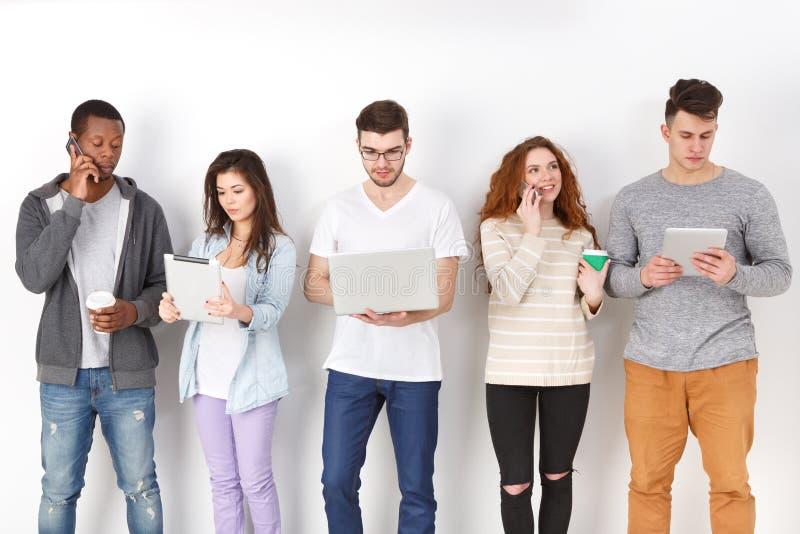 Разнообразные студенты используя устройства, стоя в линии стоковое фото