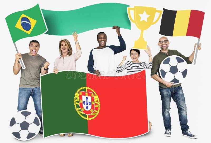 Разнообразные футбольные болельщики держа флаги Бразилии, Бельгии и Португалии стоковые фото