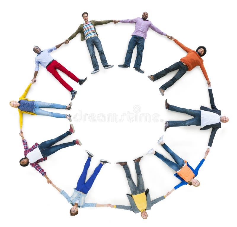 Разнообразные люди кладя вниз пока держащ руки стоковая фотография