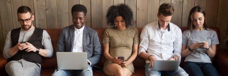 5 разнообразных парней девушек предпринимателей сидя на кресле используя устройства стоковые изображения