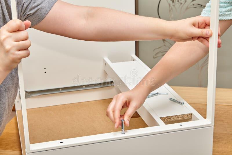 Разнорабочие исправляют часть ящика с винтами стоковое изображение rf