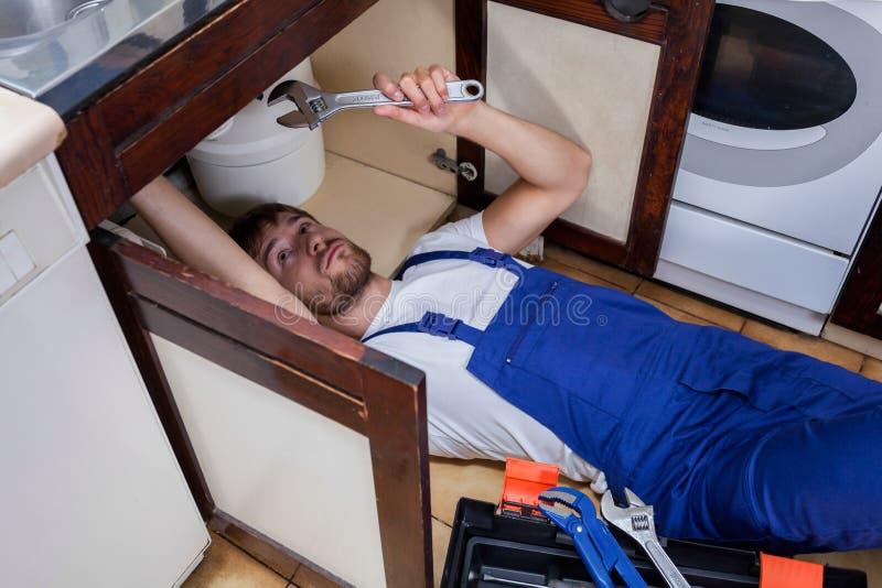 Разнорабочий во время ремонтировать кухонную раковину стоковое изображение