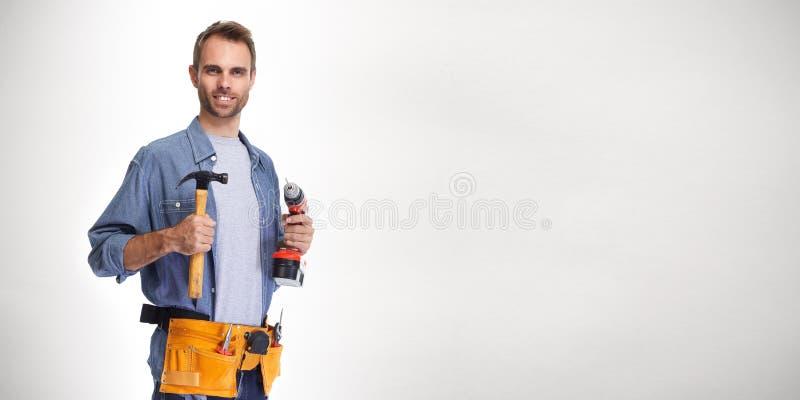 Разнорабочий построителя с сверлом и молотком стоковая фотография