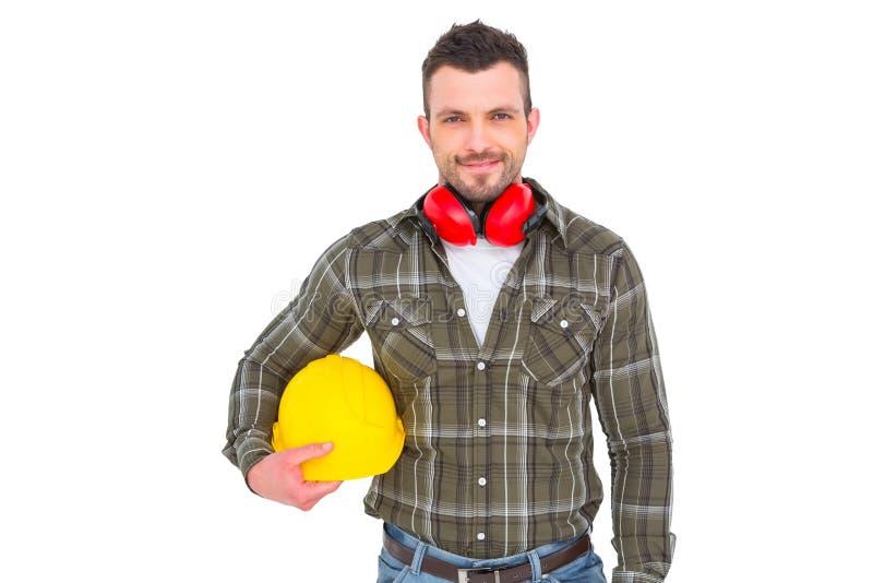 Разнорабочий при earmuffs держа шлем стоковое фото