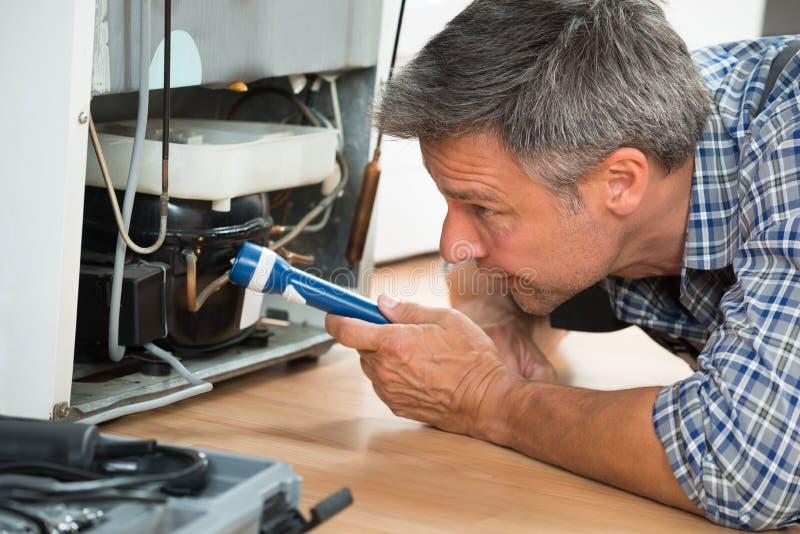 Разнорабочий проверяя холодильник с электрофонарем дома стоковые фото