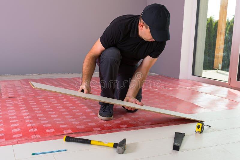 Разнорабочий устанавливая новый прокатанный пол стоковое фото rf