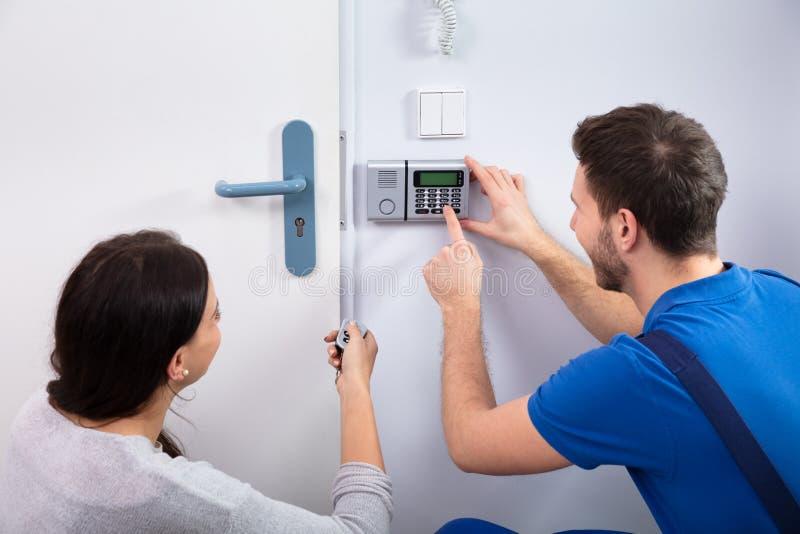 Разнорабочий устанавливая систему безопасности около стены двери стоковое изображение rf