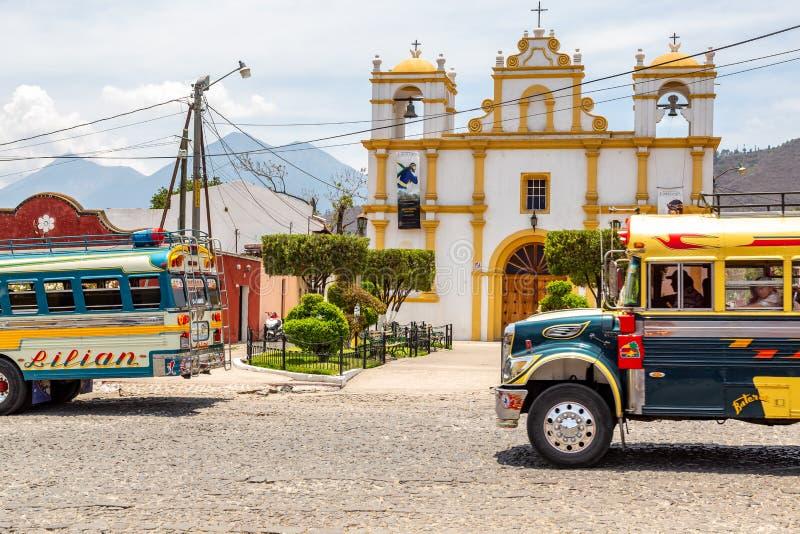 Разноцветные старые школьные автобусы используются в качестве общественного транспорта в Гватемале в церкви в Антигуа стоковые фотографии rf