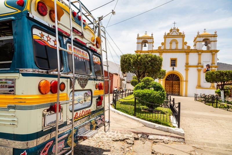 Разноцветные старые школьные автобусы используются в качестве общественного транспорта в Гватемале в церкви в Антигуа стоковые фото
