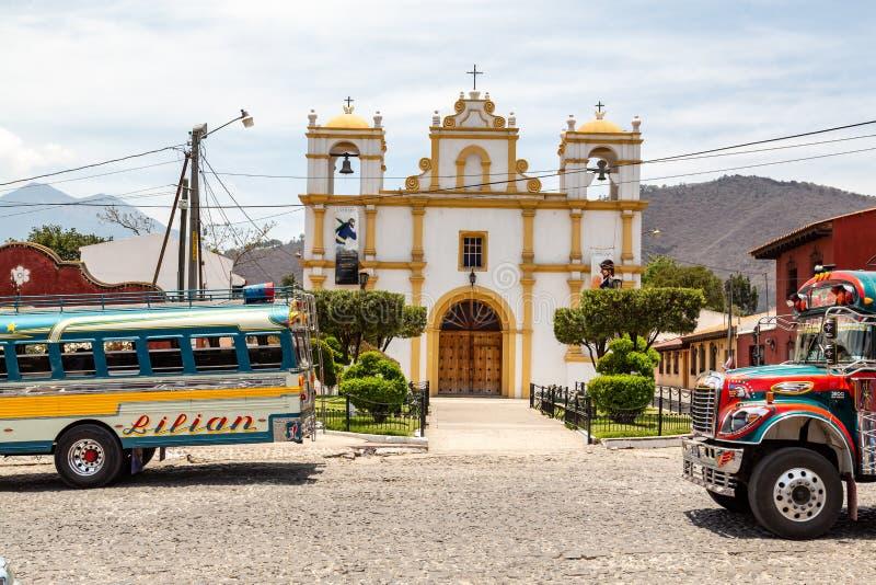 Разноцветные старые школьные автобусы используются в качестве общественного транспорта в Гватемале в церкви в Антигуа стоковая фотография