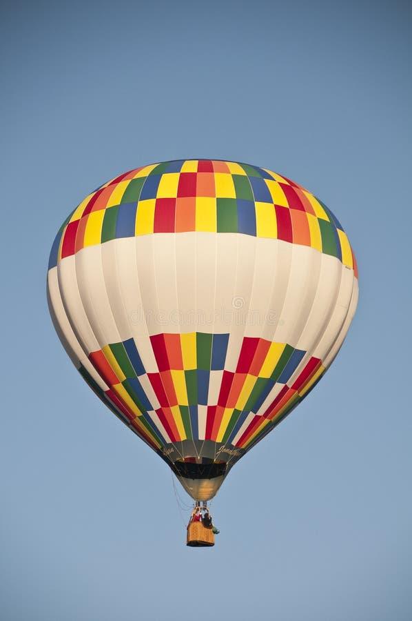 Разноцветный воздушный шар, летящий против голубого утреннего неба стоковое фото