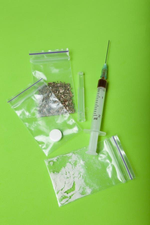 Разные виды лекарств в пакетах и шприца на зеленой предпосылке, вертикально стоковое фото