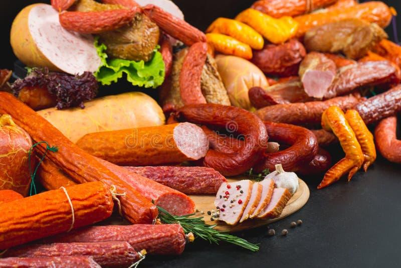 Разные виды сосисок и мясных продуктов на черной предпосылке стоковые фотографии rf