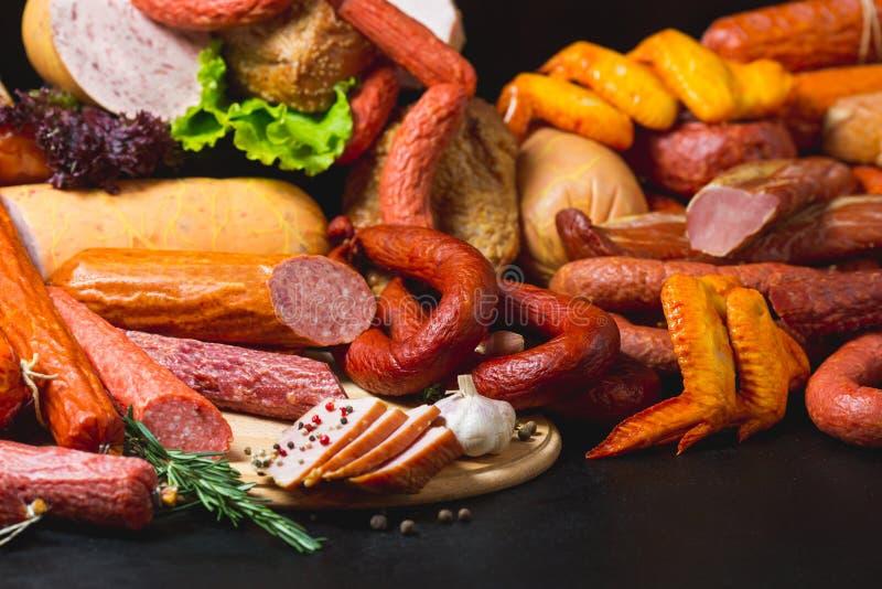 Разные виды сосисок и мясных продуктов на черной предпосылке стоковая фотография
