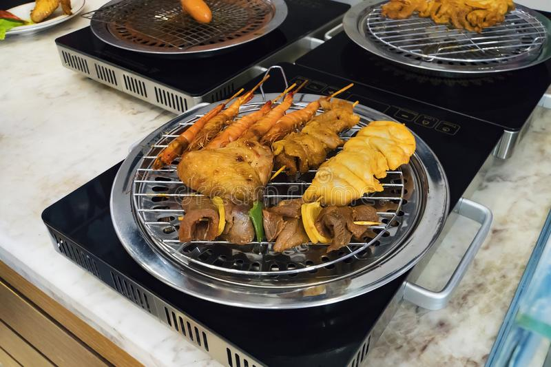 Разные виды kebabs зажарены на безопасном электрическом гриле в кухне ресторана Варить дома Зажаренная креветка, стоковое фото rf
