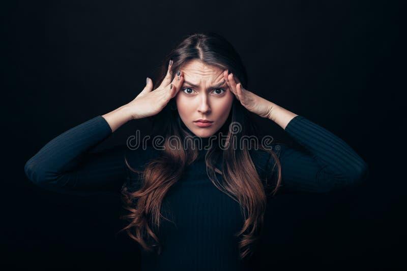 Разочарование усилило женщину касаясь голове изолированной на черной предпосылке стоковые фото