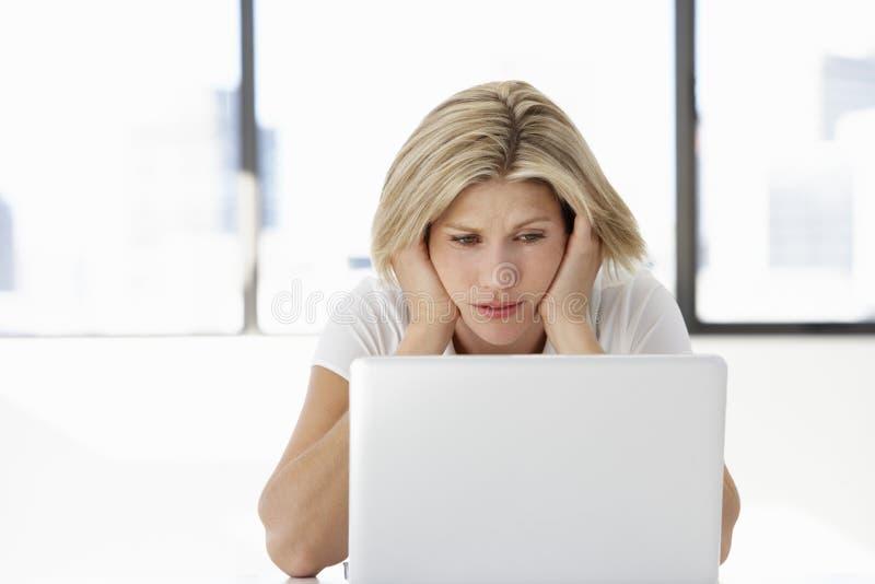 Разочарованная коммерсантка сидя на столе в офисе используя компьтер-книжку стоковые изображения