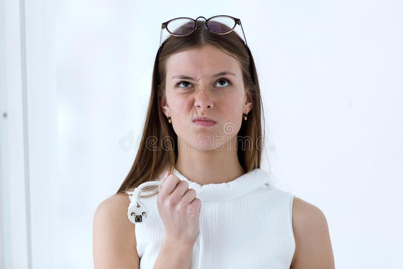 Разочарованная молодая женщина дела держа компьютер затыкает внутри офис стоковая фотография