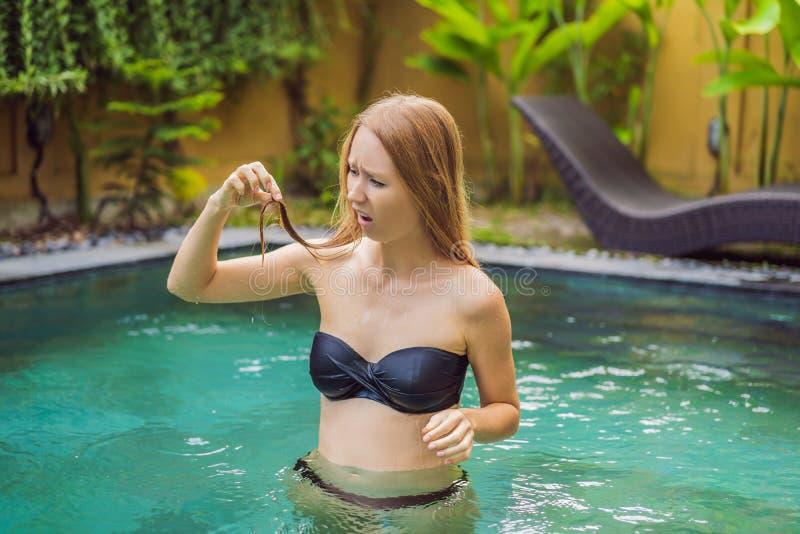 Разочарованная молодая женщина имея плохие волосы в бассейне Должный к факту что химикаты в бассейне стоковое изображение rf