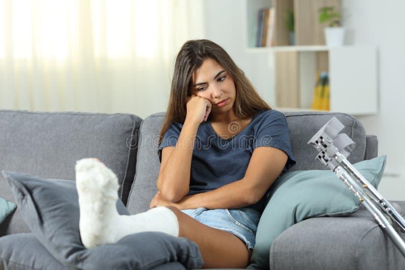 Разочарованная неработающая женщина смотря ногу гипсолита стоковая фотография rf